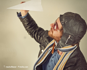 Aviator pilot with hat and sunglasses plays with paper planes